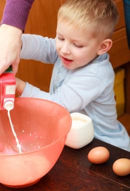 Boy Kid Baking Cake. Child Pouring Mik Into A Bowl. Kitchen.