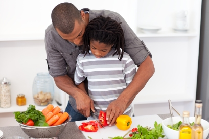Loving Father Helping His Son Cut Vegetables